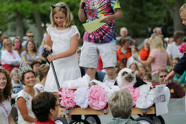 "Record-Eagle/Keith King<br /> Rachel Dunphey, 10, of Traverse City, pulls a wagon holding her family's cats, Ruby, left, and Max, with the theme, ""Just Married"" in the Best Dressed Ensemble category during the National Cherry Festival Kids' Pet Show at F & M Park in Traverse City."