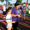 Cancer survivor Charlotte Sonntag and her 10-year-old daughter, Lexi, cut the ribbon to get the 2014 Relay for Life started Friday at Shenango High School. — Sam Luptak Jr.