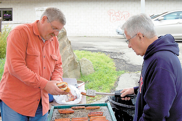 Two volunteers prepare hot dogs fresh from the grill for those who came out to Saturday's downtown tent revival staged by Vision Ministries of Lawrence County. The event took place in the parking lot of a former East North Street banquet center. — Sam Luptak Jr.
