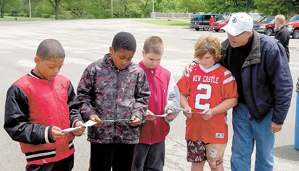 The Rev. Randy Crum explains a tract to a group of boys who came out to the revival. — Sam Luptak Jr.