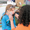 Virginia McCue, 7, gets a tatoo on her face from 13-year-old Alexis Gish.