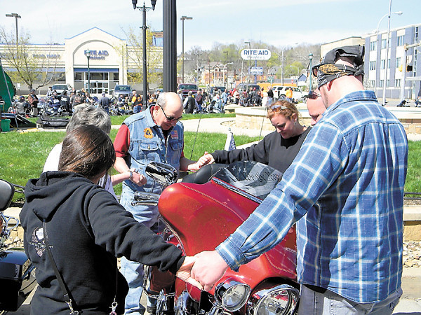 After the mass blessing, Art Terracio, center, of the Christian Motocyclists Association offers a personal prayer over a bike.