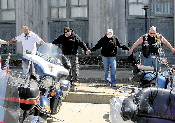 Bikers bow in prayer in front of the former post office building on the square.