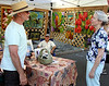 A bit like Mark Twain's Tom Sawyer, artist Anthony Casasanto sits at the back of his tent while his friend, Barry Marron, talks about his art work with Marcella Colonna at the Ambler Arts and Music Festival Saturday, June 13, 2015.<br /> Bob Raines--Montgomery Media