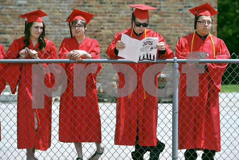 -Messenger photo by Hans Madsen<br /> <br /> Bryce Rogers studies the program Sunday afternoon while getting lined up for the 2015 Fort Dodge Senior High Graduation Commencement at Dodger Stadium. His classmates Cassidy Roberts, left, Alex Rogers and Joey Rosalez keep an eye on the stands.