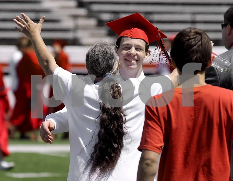 -Messenger photo by Hans Madsen<br /> <br /> Graduate Jacob Berube is about to get a big hug from his grandmother, Rebecca Hanson, of Fort Dodge, after she ran across the field to greet him following the 2015 Fort Dodge Senior High Graduation Commencement at Dodger Stadium.