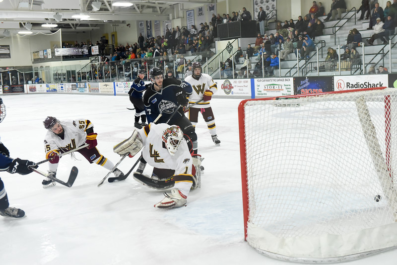 A shot by Junior Steelheads Kyle Kruenegel (not pictured) shoots past Wolverine Goalie Brendan Duff (1) only to hit the goal post and bounces back into play.  Wolverines Evan Carter (55) and Junior Steelheads Arturs Sevcenko (27) back up the play.