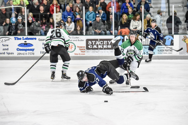 Junior Steelheads Arturs Sevcenko (27) gets tripped up by Monsters Parker Olson (12) during the first period of Saturday's game in McCall.