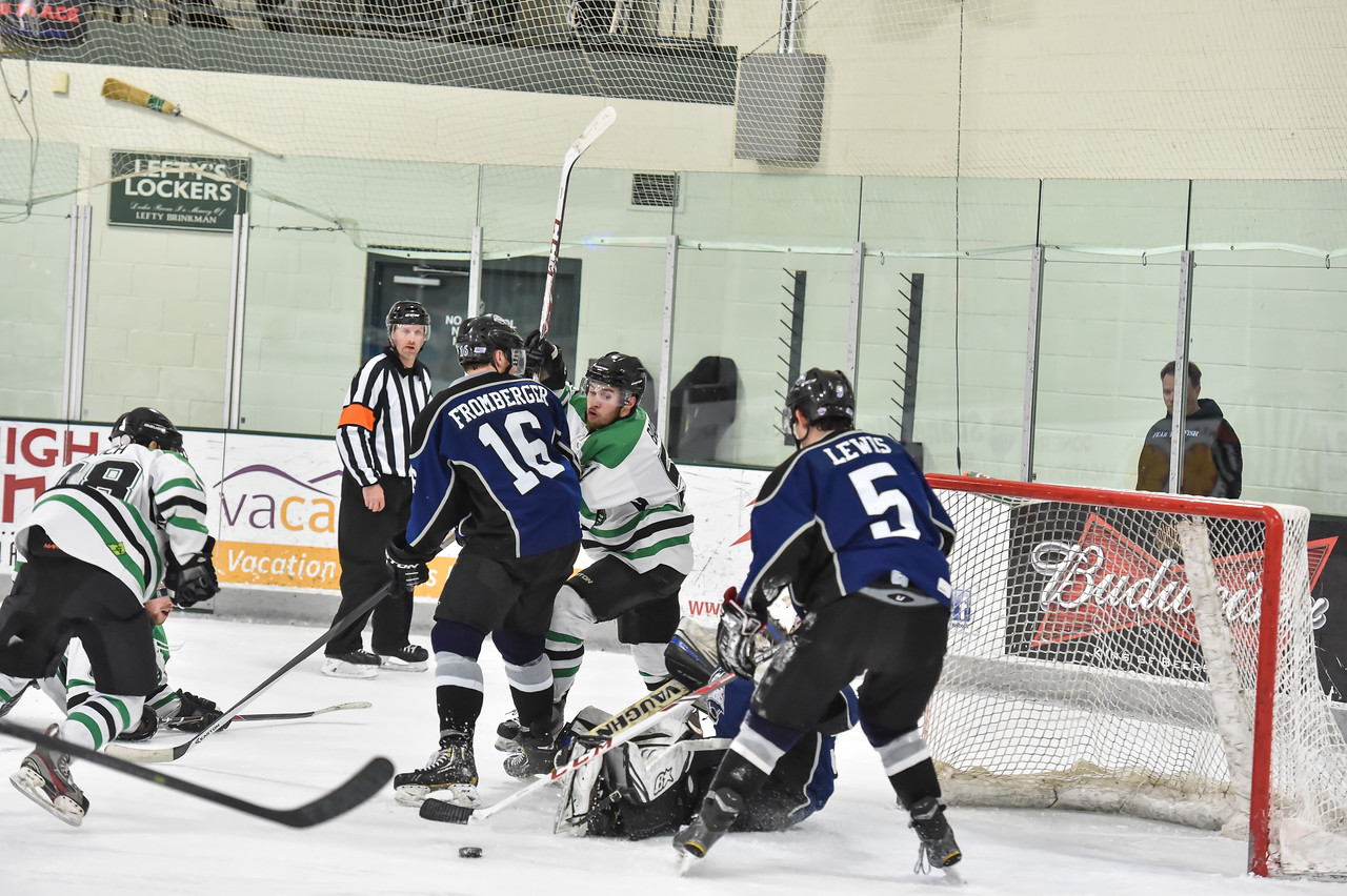 Junior Steelheads Phil Fromberger (16), Parker Lewis (5) and goalie Tyler Hough (35) successfully defend the goal from a shot by Monsters Jonathan Bengtsson (58) during the final period of Saturday's game.