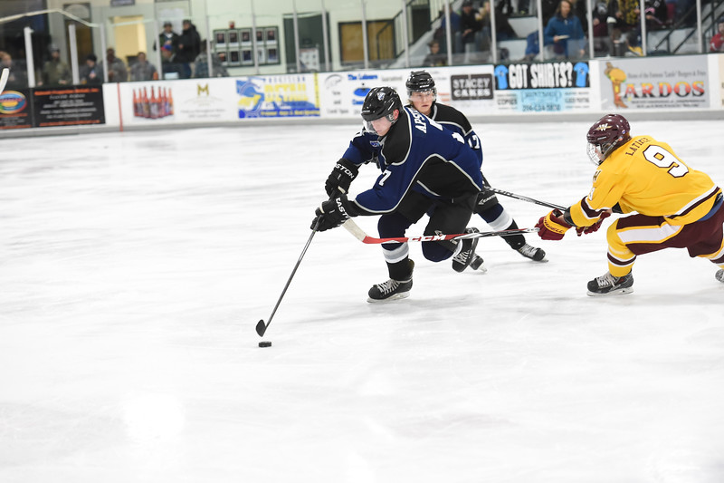Jr. Steelheads Kris Apsitis (7) drives around Wolverines Tyler Latimer (9) during the game last Friday in McCall.