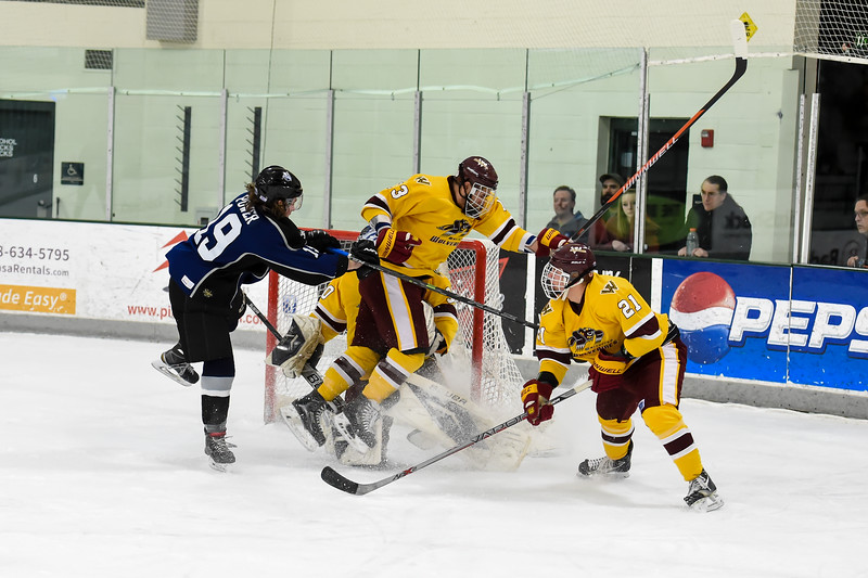 Jr. Steelheads Macky Power (19) piles into the net with Wolverines Danny Roe (13), Sam Appleby (21) and goalie Joakim Hidestrand (3) during the 2nd period of Friday's game.