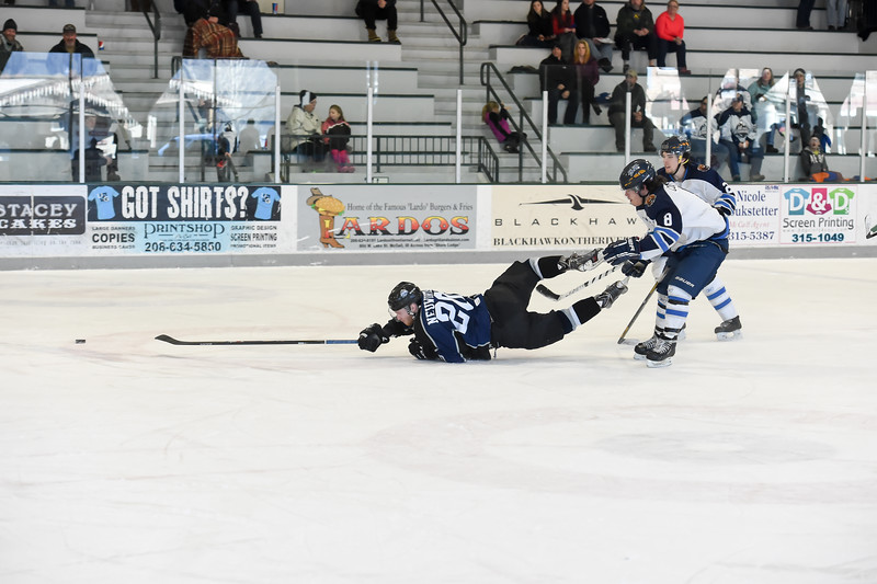 Junior Steelheads Robert Neuwirth (20) reaches, but fails, to continue his control of the puck after being tripped up by Lake Tahoe Blue's Steven Colombo (8) during Sunday's game in McCall.