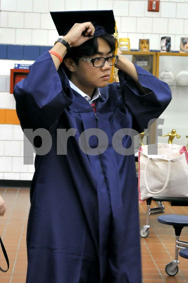-Messenger photo by Joe Sutter<br /> <br /> Bill Guan, an international student from China, adjusts his hat before the Manson Northwest Webster Graduation ceremony. Guan has been in the U.S. for about 8 months and plans to attend Iowa State University.