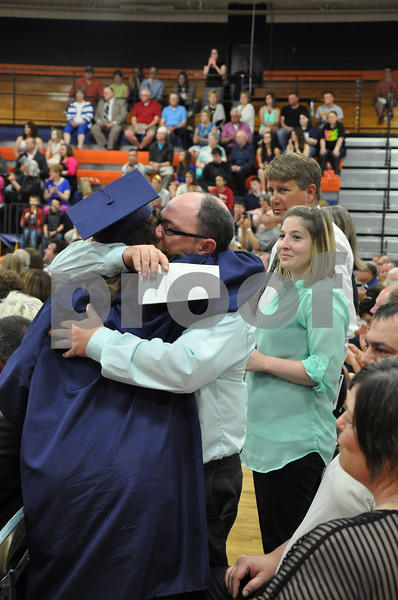 -Messenger photo by Joe Sutter<br /> <br /> Shelby Wood hugs her dad Chris Wood, with mom Bliss Wood and stepdad Dave Anderson at right. Forty-four graduates walked across the MNW stage Sunday and came out into the crowd to give roses to their parents.