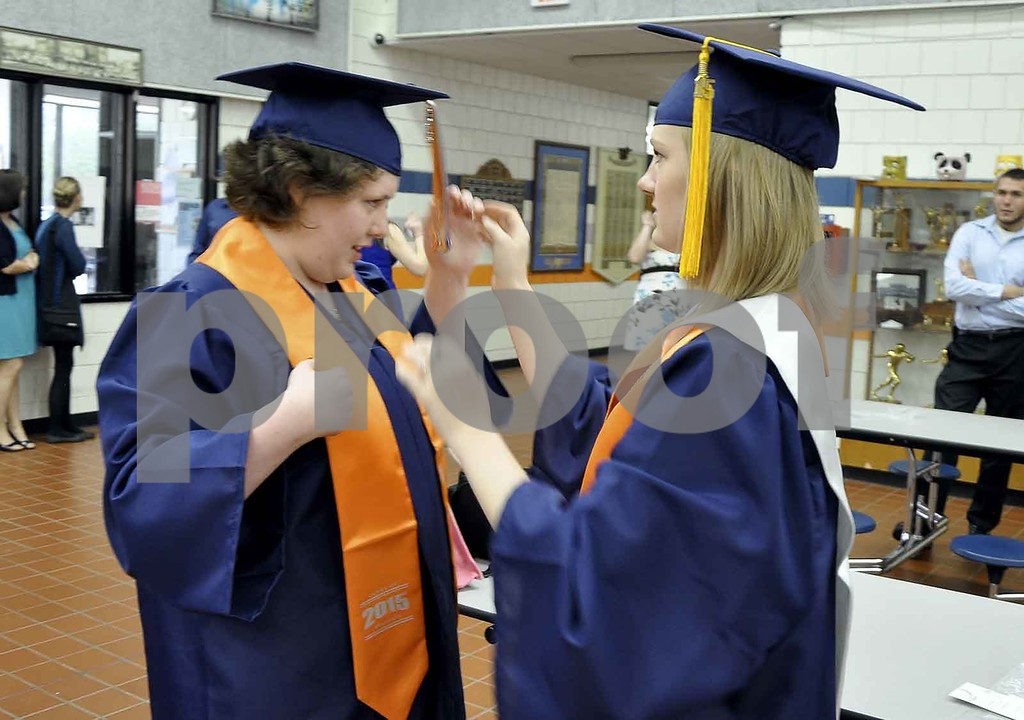 -Messenger photo by Joe Sutter<br /> <br /> Molly Johnson, left, gets a little help with her cap and tassle from Elsa Martens before the MNW commencement ceremony.