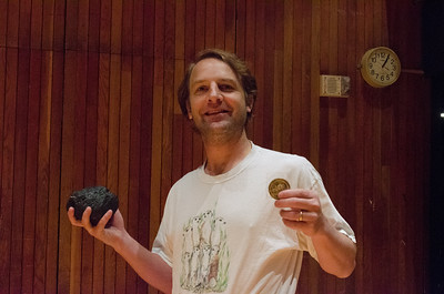 A member of Luck holding the nautilodestone and the coin