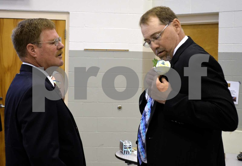 -Messenger photo by Brandon L. Summers<br /> <br /> Shannon Miller, Prairie Valley board president, right, puts on his teal-tipped white rose with some help from fellow board member John Field ahead of Southeast Valley's first graduation ceremony Sunday.