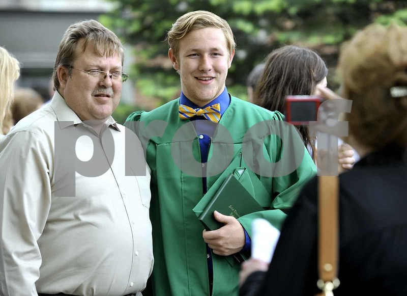 -Messenger photo by Hans Madsen<br /> <br /> Freshly minted alumni Eric Kremer, center, who selected a classic bow tie for the day, poses for a photo with his dad, Jerry Kremer following the 60th annual St. Edmond Catholic High School Commencement. His mom, Tammy Kremer, takes the photo at right.