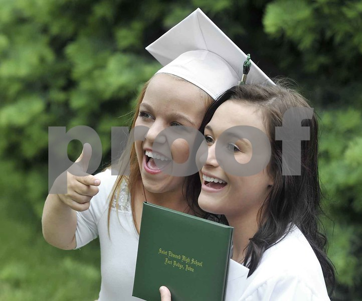 -Messenger photo by Hans Madsen<br /> <br /> Kaley Feser, 16, at left, tries on her friend Madison Julius' graduation cap Sunday afternoon following the 60th annual St. Edmond High School Commencement. Feser will be graduating with next year's class of 2016.