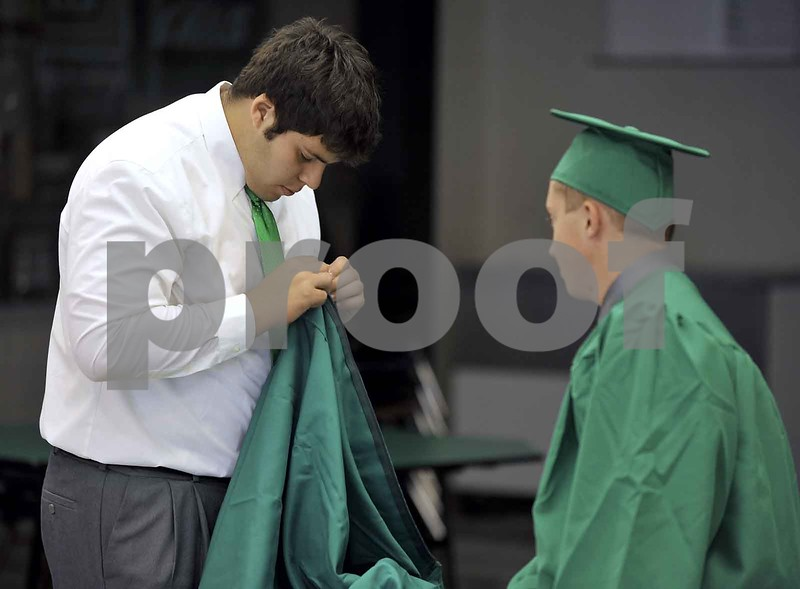 -Messenger photo by Hans Madsen<br /> <br /> Chad Remsburg, at left, has a little trouble with the zipper on his gown Sunday afternoon while trying to get dressed for the 60th annual St. Edmond Catholic High School Commencement. His friend Noah Klemp, right, watches while he gets it unstuck.