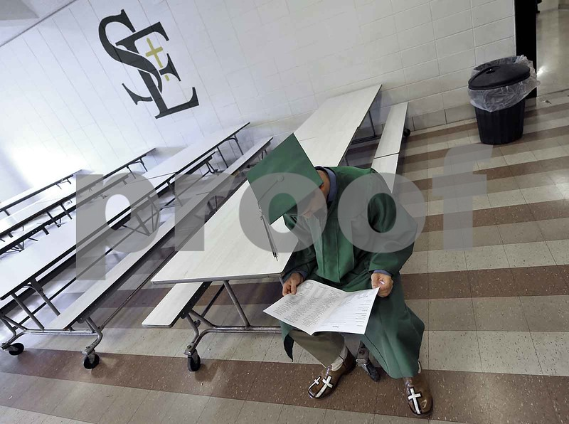 -Messenger photo by Hans Madsen<br /> <br /> Levi Hopkins studies the program Sunday afternoon while waiting for the 60th annual St. Edmond Catholic High School Commencement to get started.