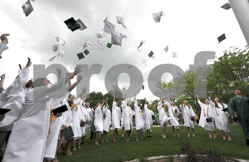 -Messenger photo by Hans Madsen<br /> <br /> Members of the Class of 2015 follow the gradition of tossing their caps into the air around the flagpole Sunday following the 60th annual St. Edmond Catholic High School Commencement.
