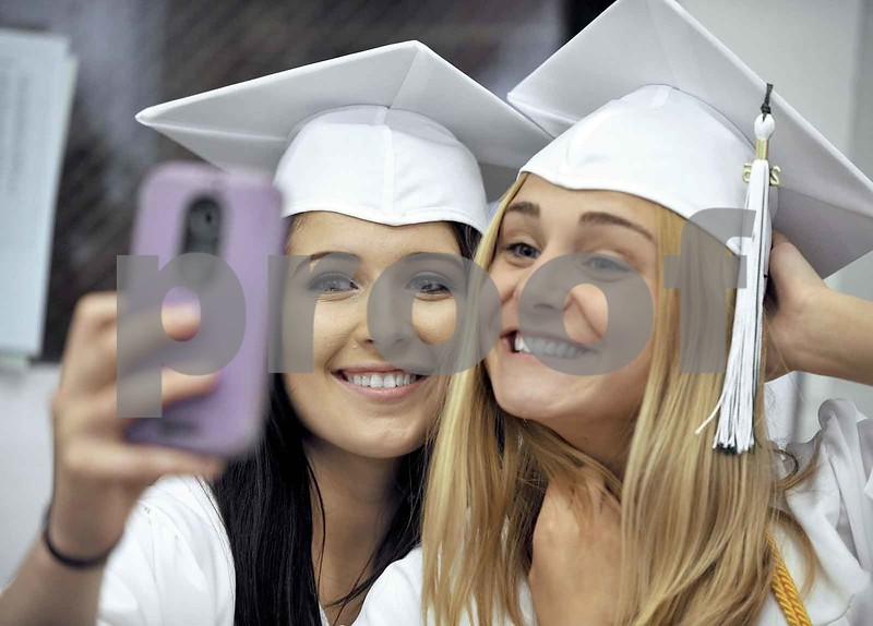 -Messenger photo by Hans Madsen<br /> <br /> Mackensie Brennan-Rowe, left, is all smiles as she poses for a cell phone picture Sunday afternoon with her fridn Bailey Baker, right, as they get ready in the St. Edmond High School library for the 60th annual Commencement.
