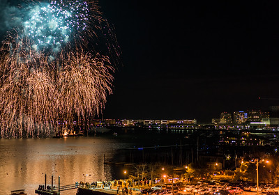 A barge sets off fireworks over Boston Harbor for New Year's 2015 as crowds watch from the waterfront
