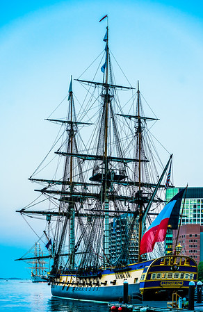 L'Hermione, a French tall ship, with lighted Sagres, from Portugal in the background