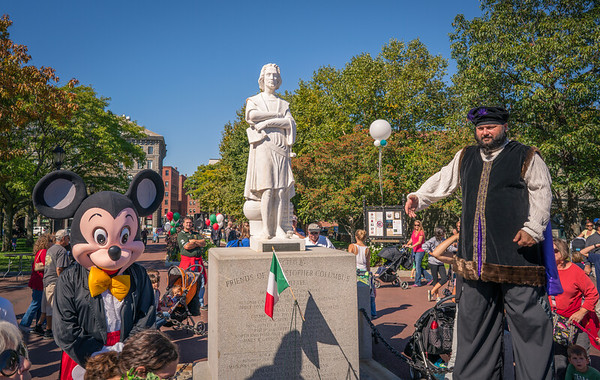 Mickey Mouse and Columbus on stilts at the Christopher Columbus statue