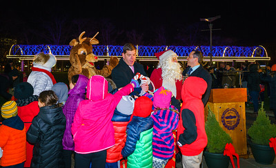 Mayor Walsh and friends throw the switch to turn on the holiday blue lights on the trellis
