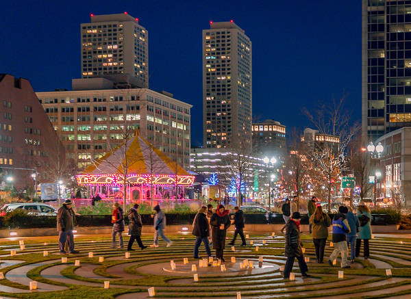 With the lighted Greenway carousel in the background, people take a break from the holiday rush by walking the labyrinth