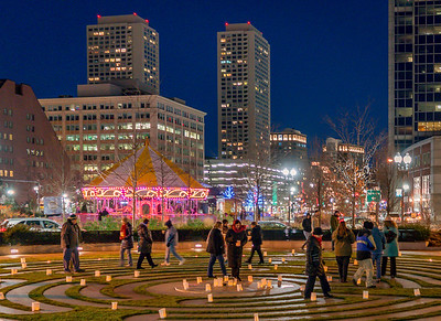 With the bright Greenway carousel in the background, people take a break from the holiday rush by walking the labyrinth