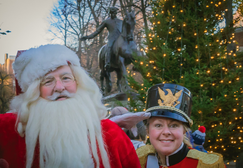 Santa and helper in front of Paul Revere and the Prado Christmas tree