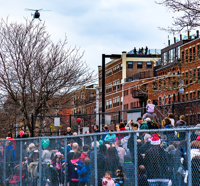 Crowds watch the helicopter come in over the North End rooftops