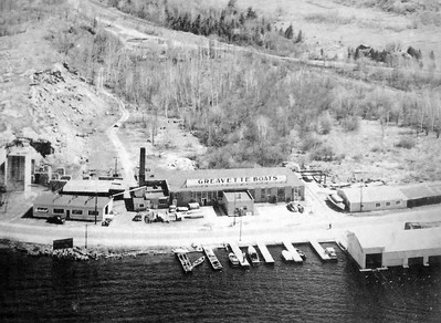 This historic photo shows the Greavette Boats Ltd. facility in the 1940's in Gravenhurst, Ontario. Production moved from left to right, with finished boats or prototypes being transported to the water by rail from the right end of the main building. The buildings have since disappeared, and the site is now part of the Gravenhurst Wharf complex, with two waterside restaurants occupying the space. An athletic complex occupies the level area behind the buildings, providing space for a Field of Dreams during the annual boat show.