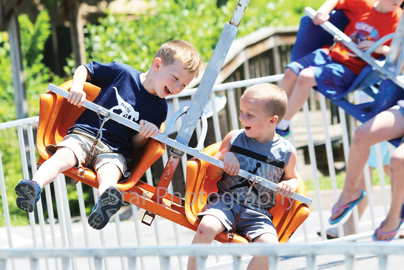 Star Photo/Curtis Carden<br /> Nate Pippin, left, and Tyson Elliott enjoy one of the rides available on Kid's Island Friday.