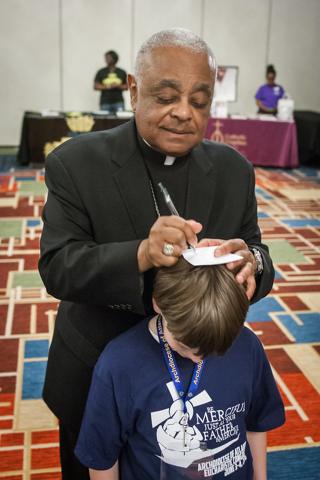 Archbishop Wilton D. Gregory uses the head of a young autograph seeker to sign his name during day two of the Eucharistic Congress. Photo By Thomas Spink