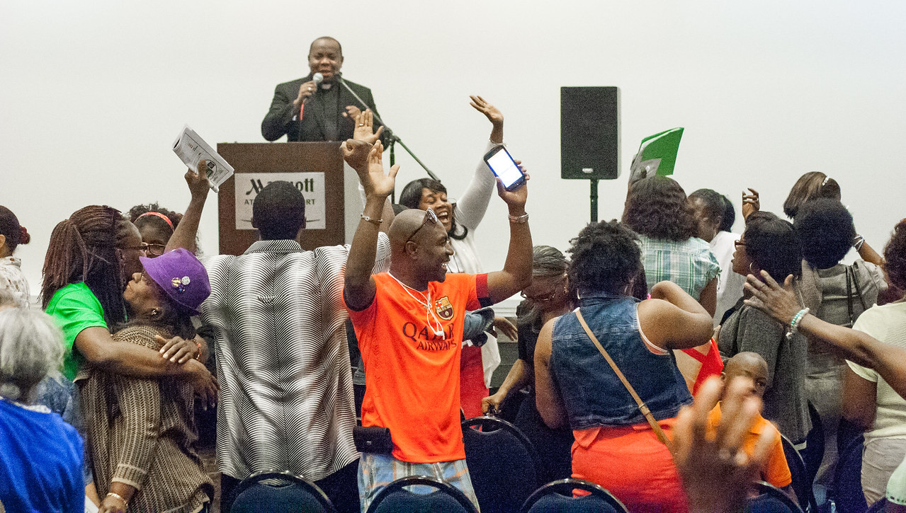 Participants in the Francophone track dance and sing to hymns of praise and worship during the first day of the 2016 Eucharistic Congress. Standing at the podium in the background is Father Cyprien Emile, the Francophone track speaker. Photo By Thomas Spink