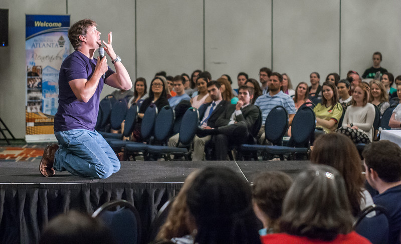 """Doug Tooke dramatically shares his message of engaging with the Catholic faith before an audience at the REVIVE young adult track at the 2016 Eucharistic Congress. Tooke, director of youth ministry in the Diocese of Helena, Montana, told the young adults of their faith, """"Now is your season. Right now."""" Photo By Thomas Spink"""