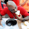 Don Knight | The Herald Bulletin<br /> AFD's Sherman Carter competes in the jelly doughnut eating contest during the  Guns & Hoses competition between Madison County police and fire departments at Hoosier Park on Saturday. The score was tied 2-2 going into the doughnut competition. The firefighters edged out the police officers to claim this year's title.