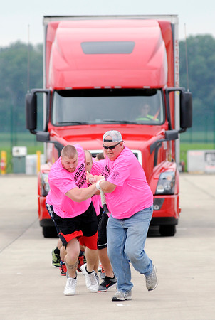 "Don Knight | The Herald Bulletin<br /> Boomer Freeman, right, and Matt Mills lead ""Madison County's Finest"" during the United Way's annual Truck Pull at the Anderson Municipal Airport on Saturday. The team made up of law enforcement from Madsion County defeated the Muncie Fire Department to win the men's division and also set a new record of 19 seconds."