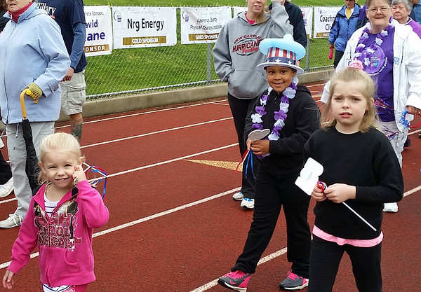 Kayliegh Gibbs, 4, left; Alexandra Heasley, 8, right; and Mallrie Brest, 7, with hat walk the Relay for Life Survivors Lap with Brenda Brest, rear right. Matthew Greco, 7, also was part of group.
