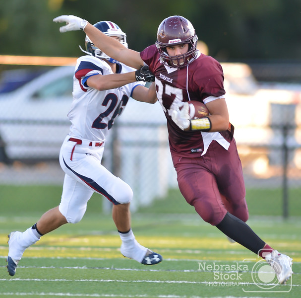 Aaron Beckman/DailyNews  <br /> <br /> Norfolk's Logan Strom attempts to outrun Lincoln North Star's Brandon Yost Friday night in Norfolk.