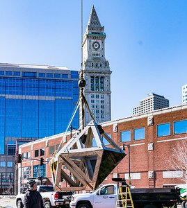Down the block from the Custom House tower, a crane lifts the sculpture pieces