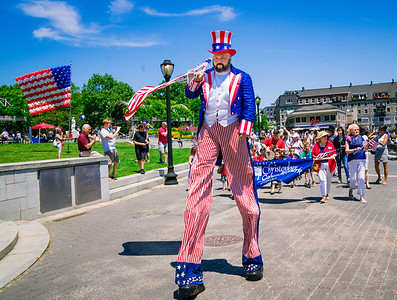 Uncle Sam on stilts leads the Independence Day parade at Christopher Columbus Park
