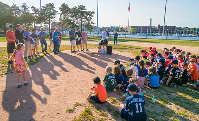 Players and coaches gather on the field at Langone Park