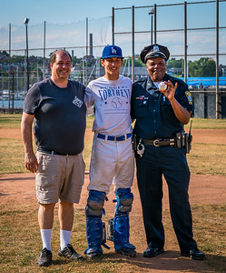 Police Officer David Saddler from District A-1 CSO office after throwing first pitch with tournament organizer John Romano and North End catcher
