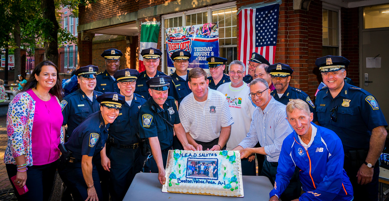 Boston Police gather around the cake for BPD Area A-1 with Mayor Walsh, BPD Commissioner Evans, NEAD members and Councilors LaMattina and Essaibi George