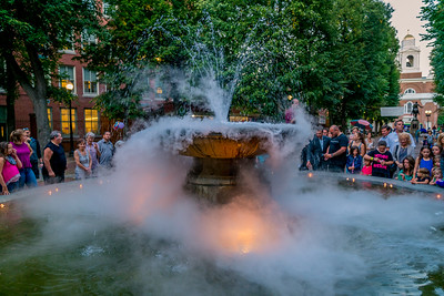 Candle lighting ceremony at the smokey Prado Fountain for National Night Out